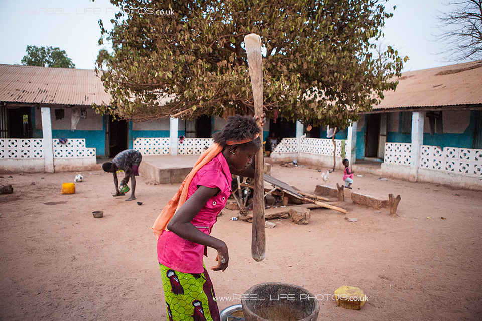 Gambian girl pounding the uncooked rice to remove the inner husk