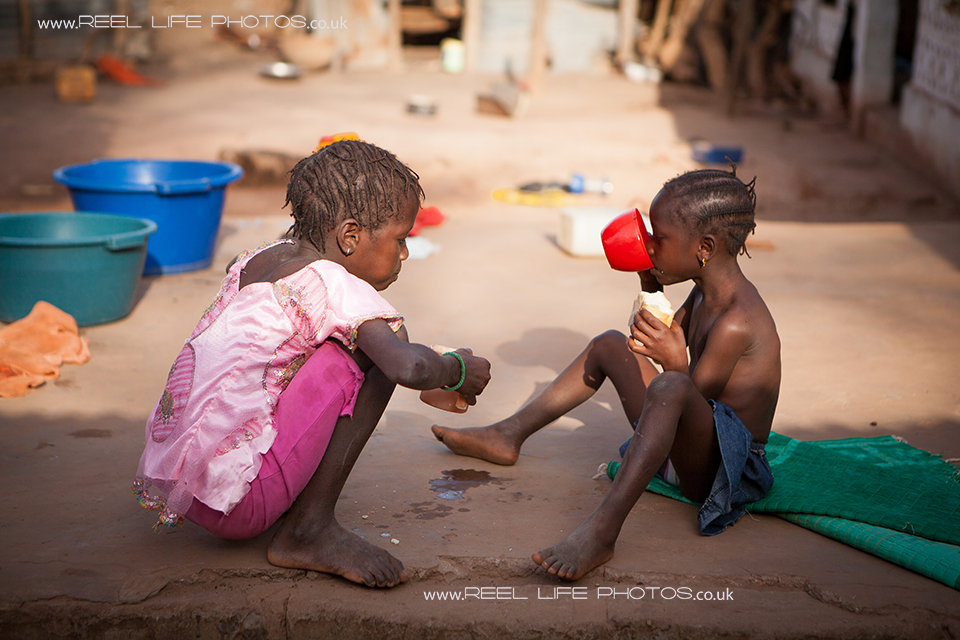 Gambian children drinking water in the village of Jorem
