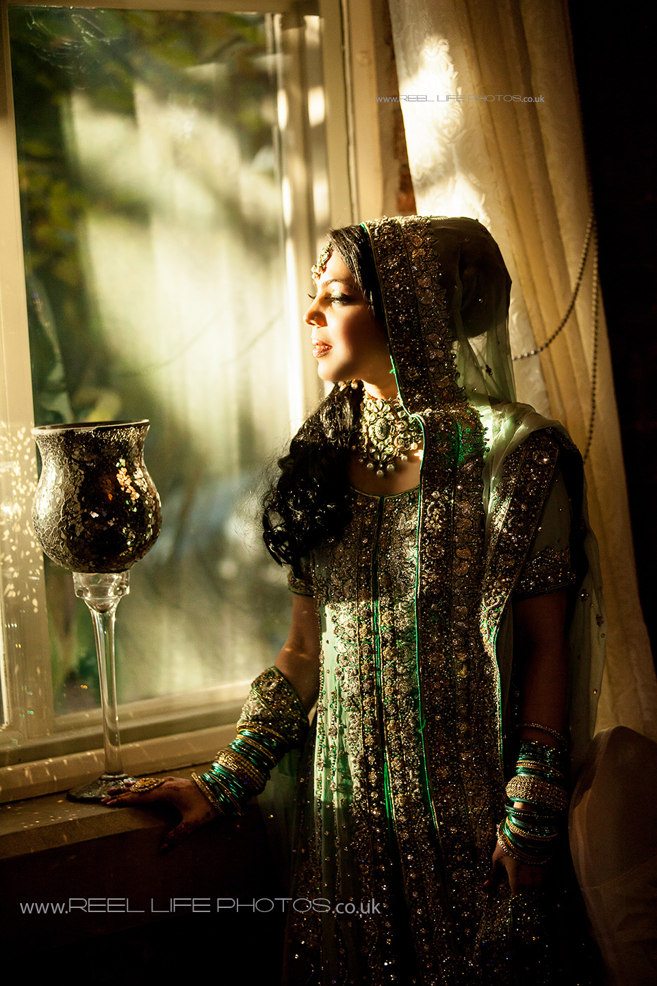 Asian bride by the window at sunset