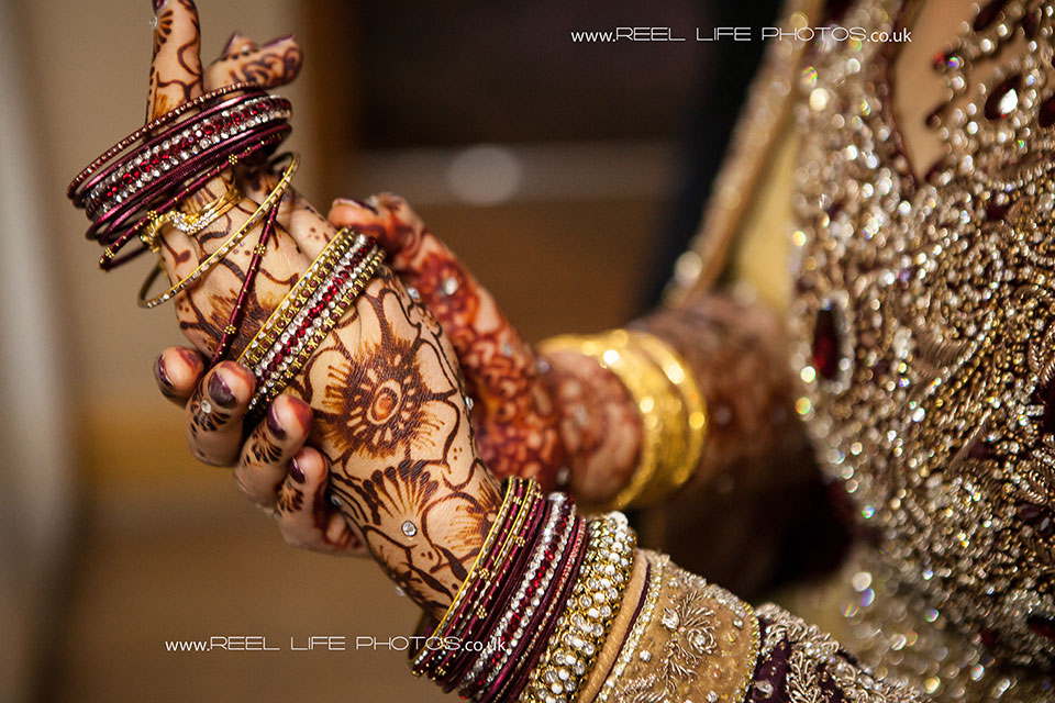Asian wedding with the bride putting on her bangles