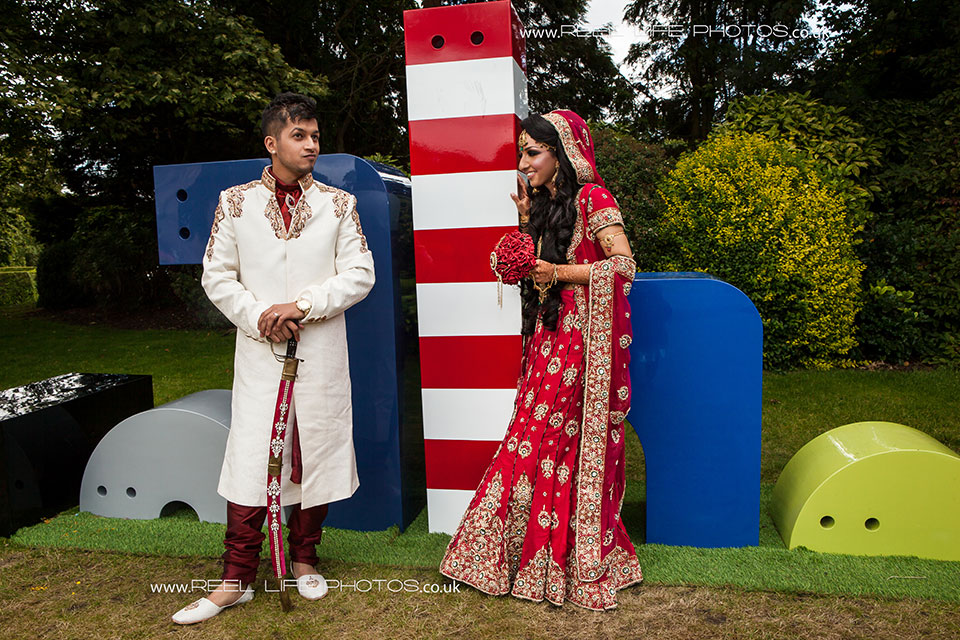 Asian bride and groom in traditional Indian dress against modern sculptures in Bradford