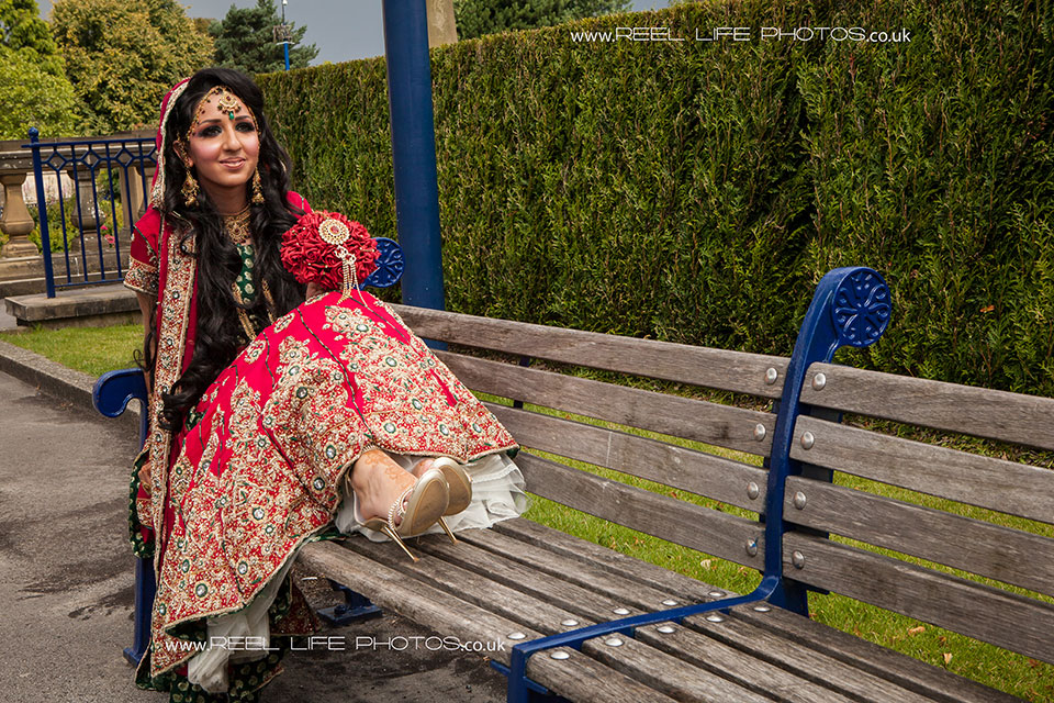 picture of Asian bride after her wedding in Bradford, sitting on a bench in Manningham Park.