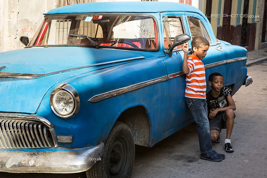 Real life in Cuba - old classic car and Cuban kids.