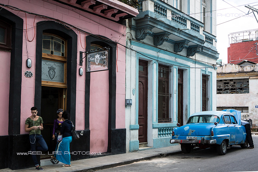 Real life in Cuba - classic cars and young people hanging out/