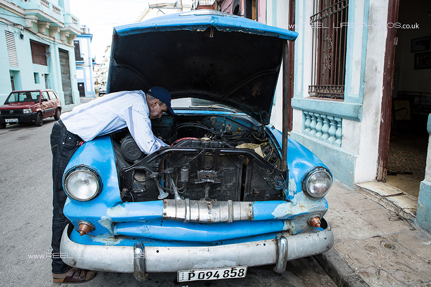 Real life in Cuba - man repairting his old American car in Havana