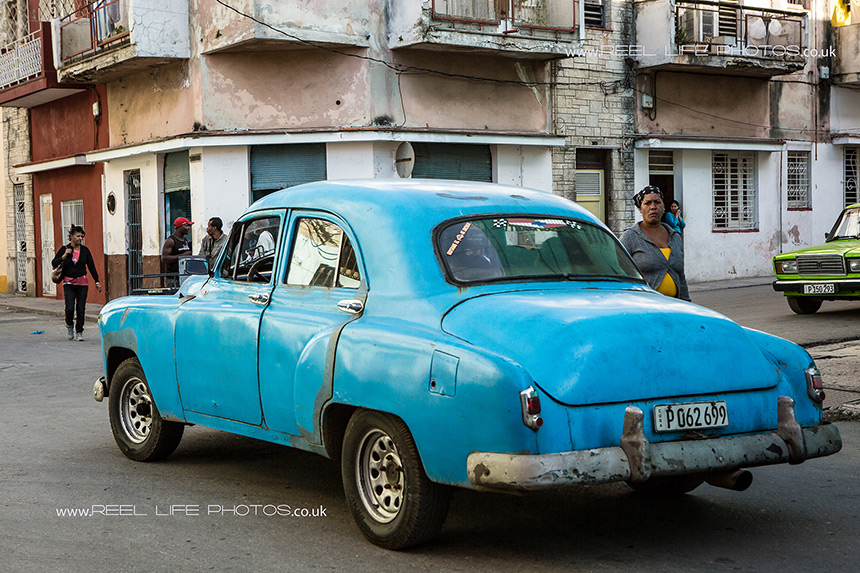 Cuban street life with classic car and local Cubans.