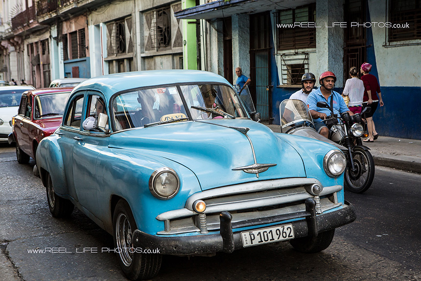 Real life in Cuba .  Classic cars an old motorbikes.