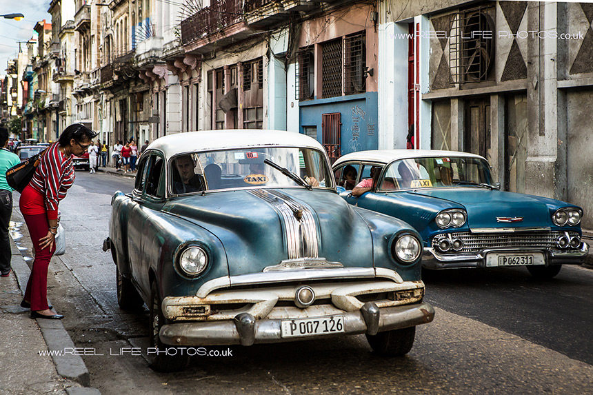 Woman hailing a share taxi in Old Havana.