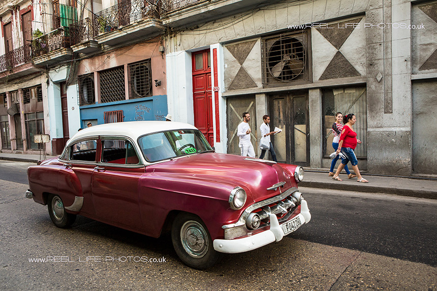 Street in Cuba with red classic taxi car in Old Havana