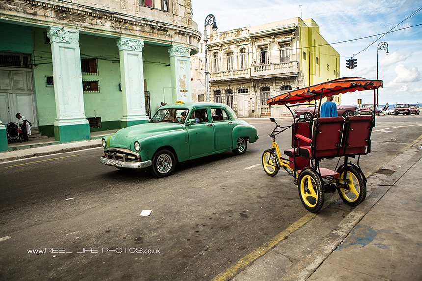 Rickshaw and old American car in Cuba
