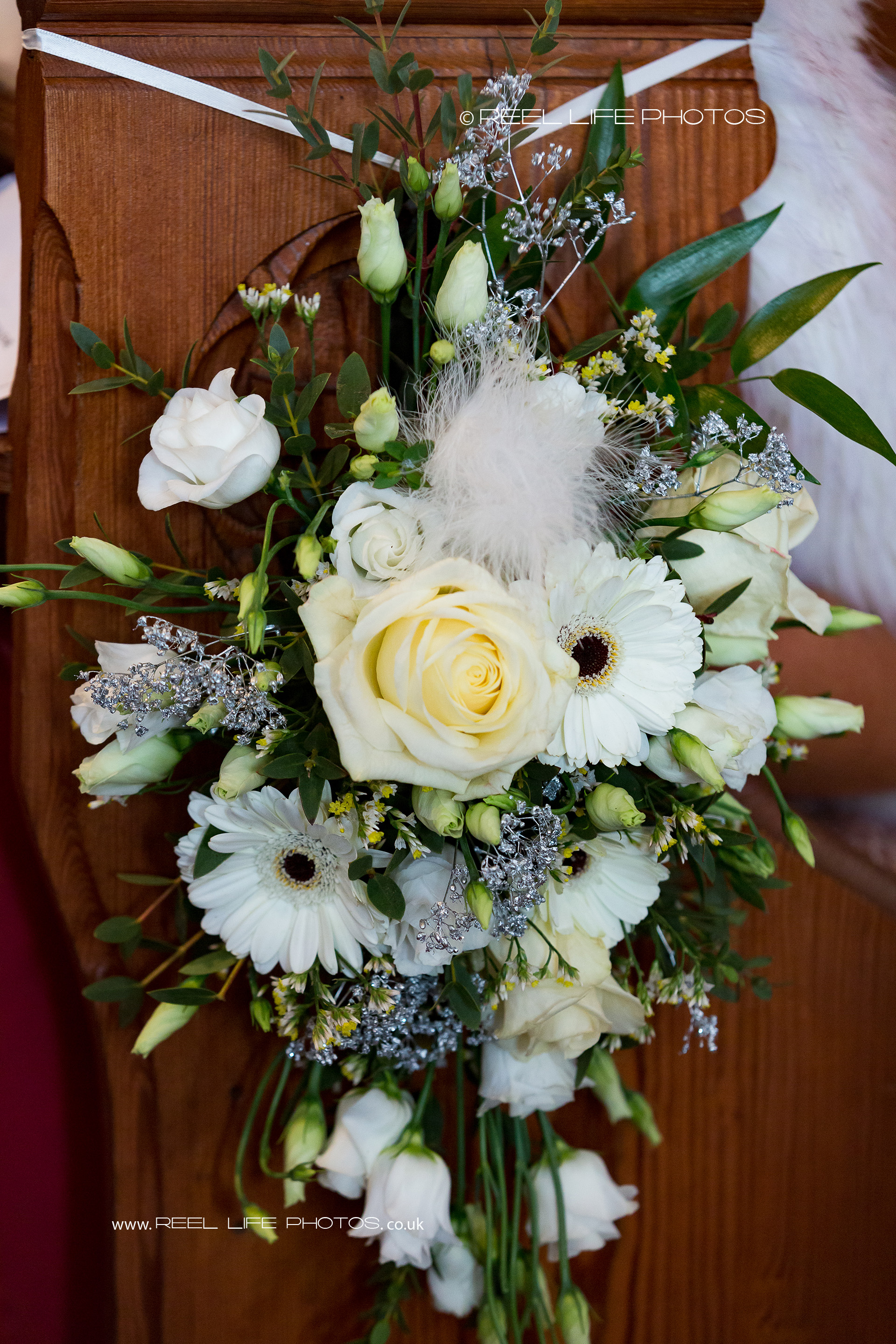 Beautiful floral arrangements decorate the sides of the church pews