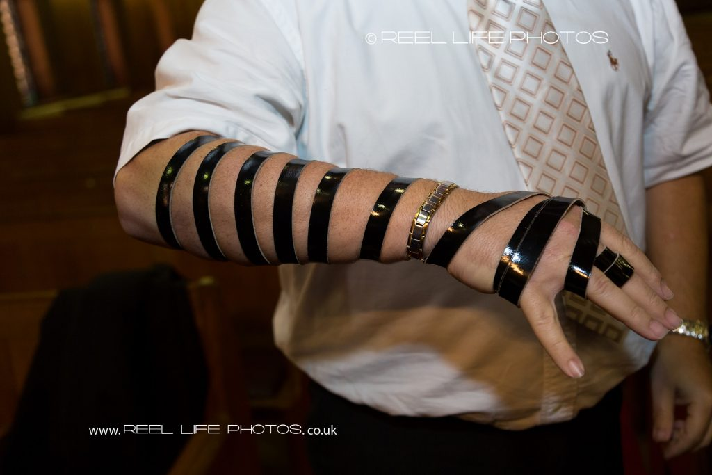 Tefillin - wrapped leather straps on arm and hand of adult male Jew