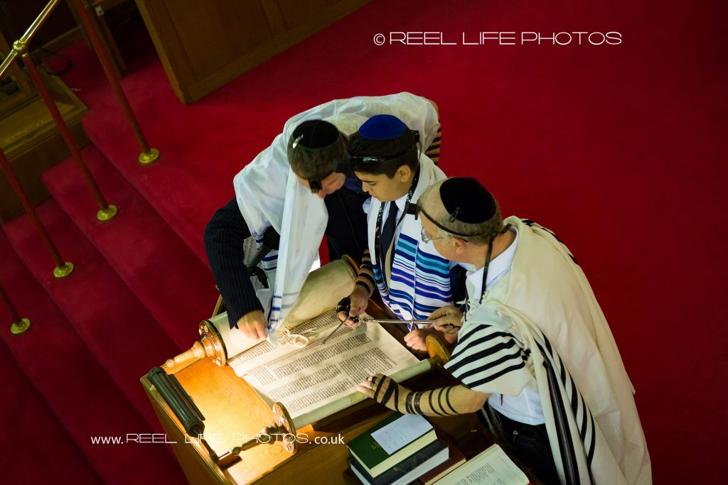 3 Jews reading passages from The Torah during Tefillin at Jackson Row Synagogue