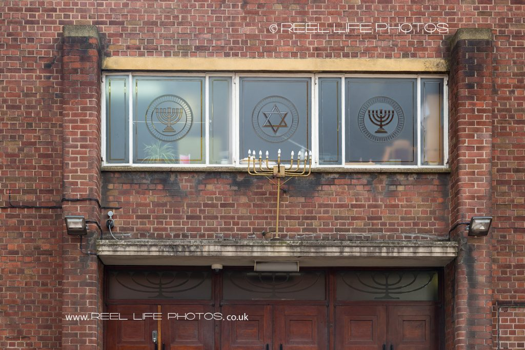 Jewish Star of David and 7 branch candlestick symbols set in windows of Synagogue