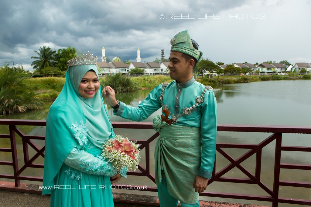Malaysian bride and groom on their wedding day by the lake at Kelab Merbok Laguna