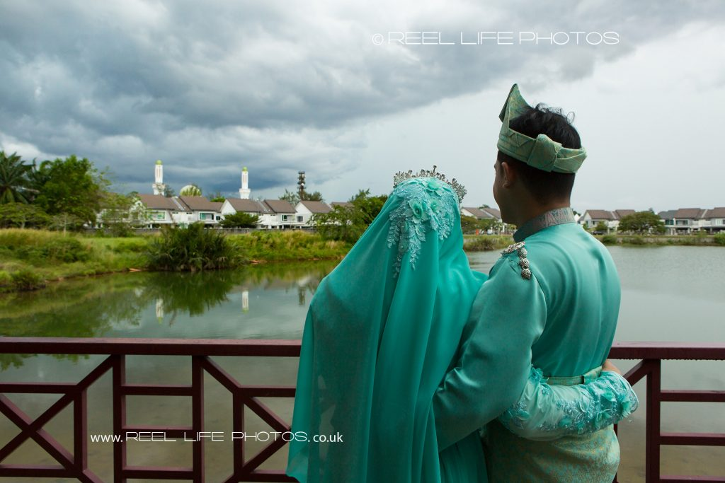 Malaysian bride and groom on their wedding day looking out at the lake at Kelab Merbok Laguna, just before the rain comes down.