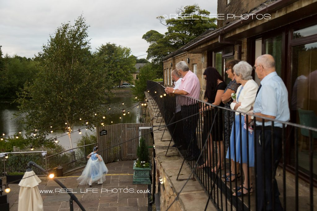 Waterton Park Hotel evening wedding reception guests looking down on the patio from the balcony towards the lake, as a little bridesmaid walks past