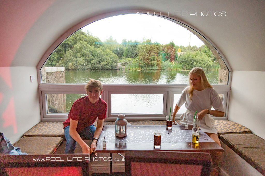 The arched window overlooking the lake at evening wedding reception at Waterton Park Hotel with natural picture of two guests seated there.