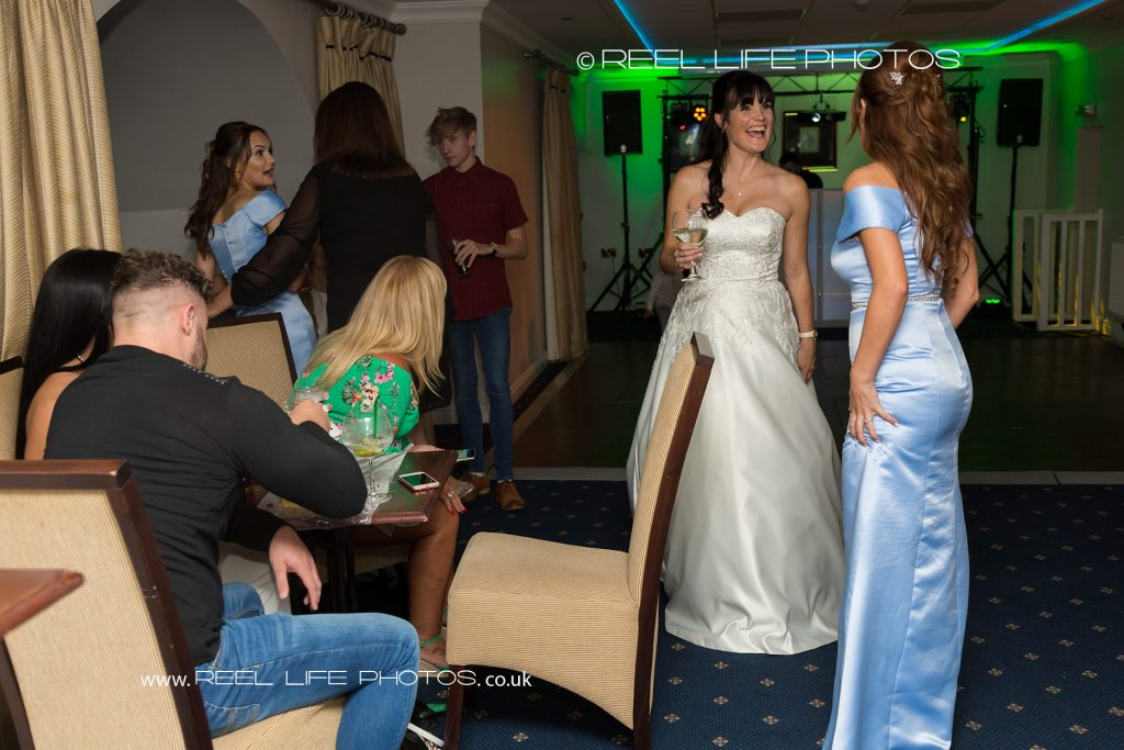The bride chats with her friends during the evening wedding reception at the back of Walton Hall in Wakefield