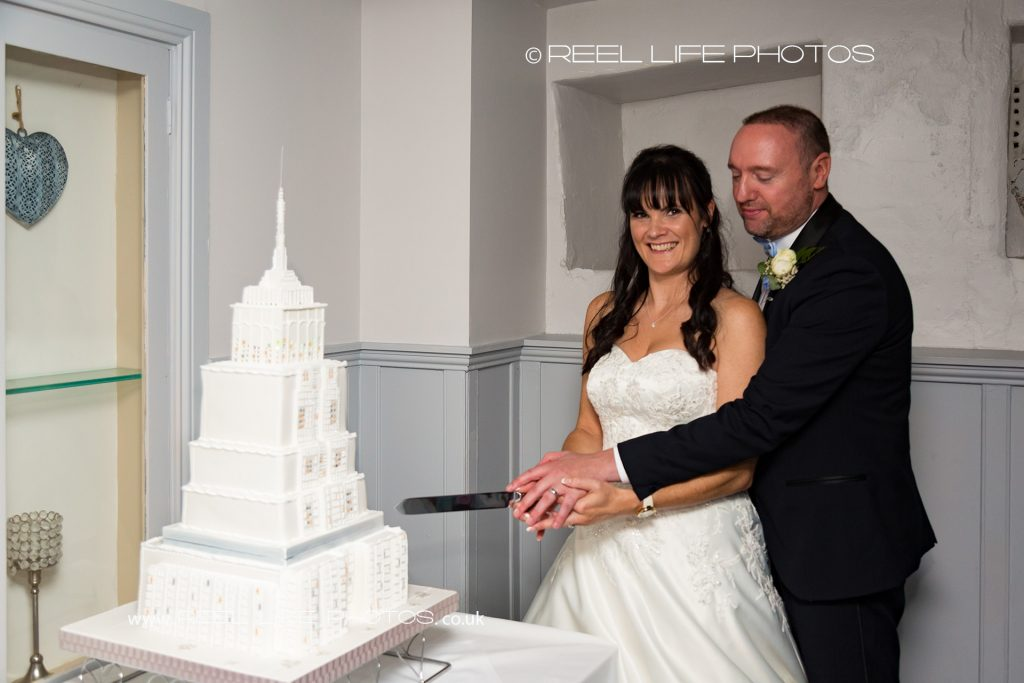 Cutting the Empire State Building wedding cake at evening wedding reception at Waterton Park Hotel