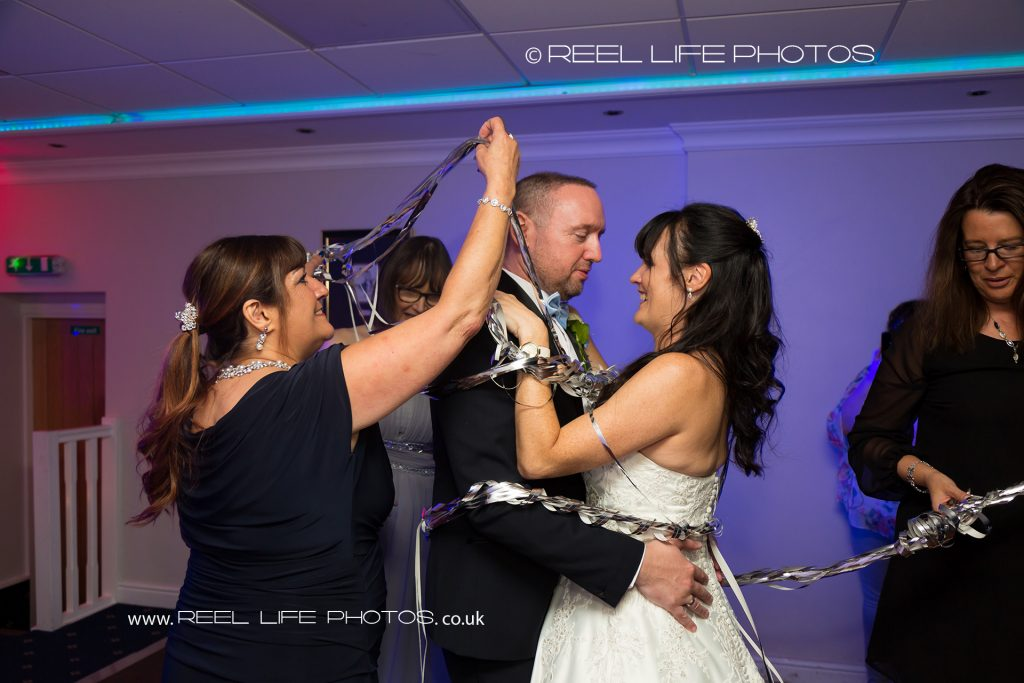 The bride and groom are trying to do the first dance but the are ambushed by guests wrapping them in silver ribbons at evening wedding reception at Waterton Park Hotel