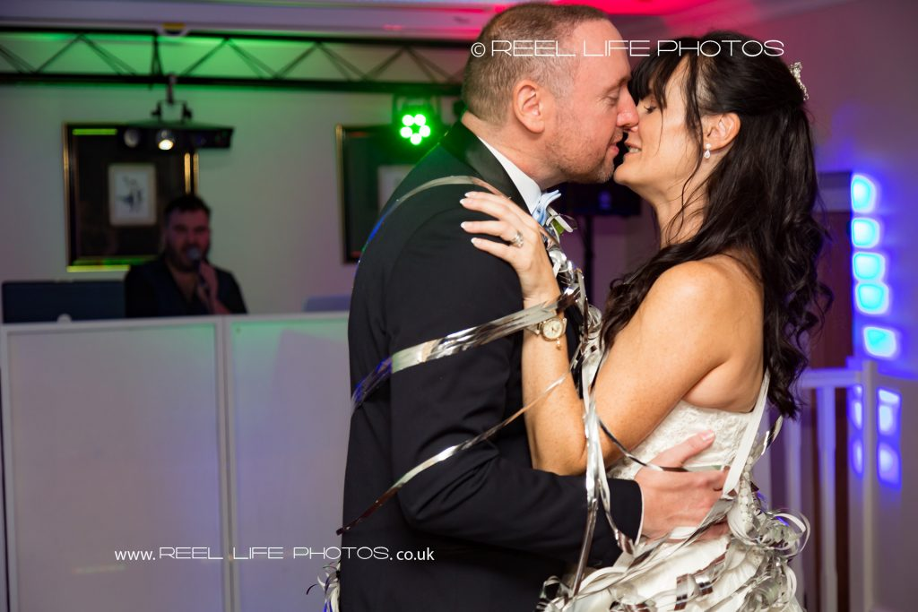 The bride and groom manage a kiss  at the end of their first dance, despite being wrapped up in sliver ribbon, at evening wedding reception at Waterton Park Hotel