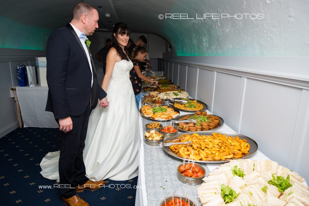 The bride and groom at their evening wedding reception buffet at Waterton Park Hotel