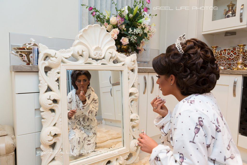 16 year old traveller bride getting ready  for her wedding, applying lip gloss in front of an ornate mirror inside the chalet where her mother lives.