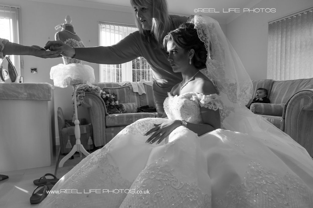 natural black and white wedding picture as the hair and make up artist reaches out to take a hairpin  from the traveller bride's mother