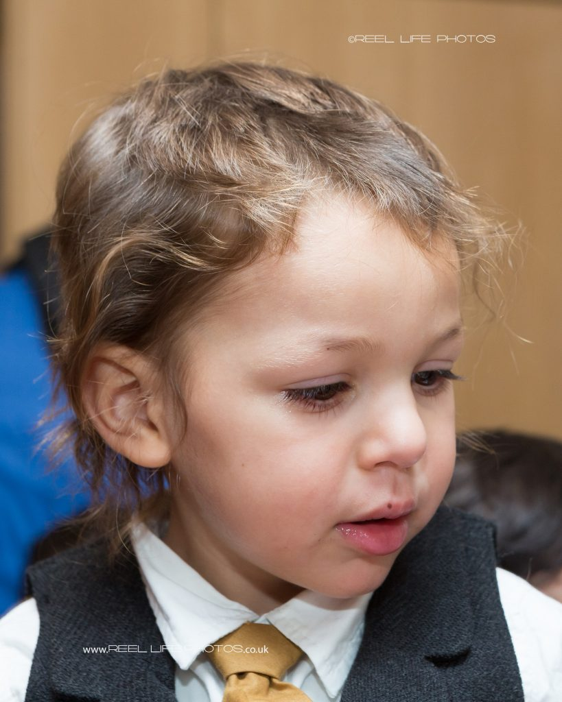 A three year old Romanian boy has his very first haircut, at a traditional party in front of all the family and friends, captured in a natural documentary style of photography.