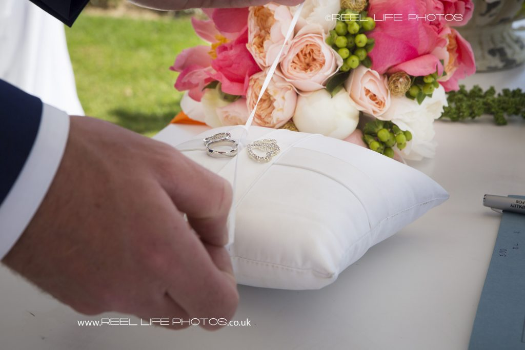 Wedding rings on a white cushion during wedding ceremony at the Olympic Lagoon in Cyprus