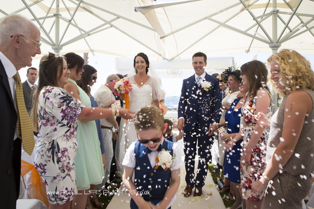 Happy confetti picture after beach wedding ceremony