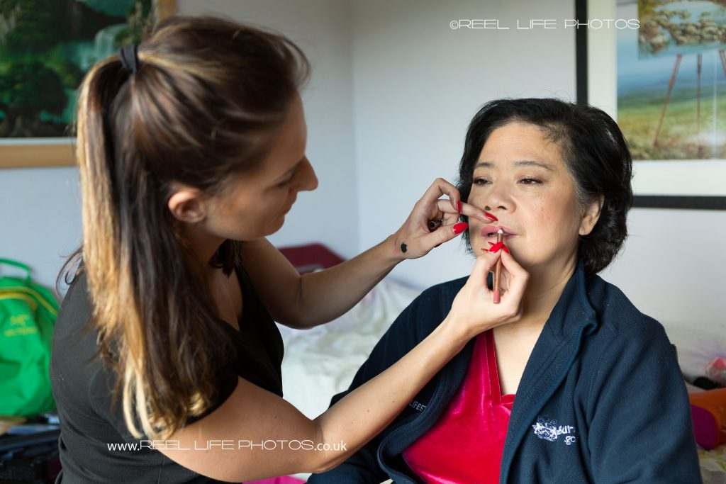 The MUA (Make Up Artist) paints the mother of the bride's lips